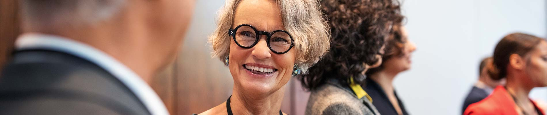 Woman with glasses smiles at networking event